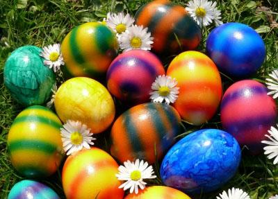 Bunte Eier und Gänseblümchen auf dem Rasen