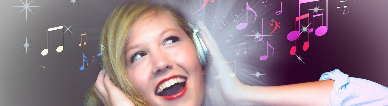 Eine junge Frau drückt sich freudestrahlend Kopfhörer an die Ohren. leuchtende Strahlen durchdringen die eine Hand und hinterlassen bunte Noten und Musikschlüssel