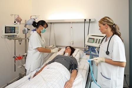 Patientin mit Tracheostoma und Beatmungsapparatur im Krankenhausbett, zwei Schwestern daneben.