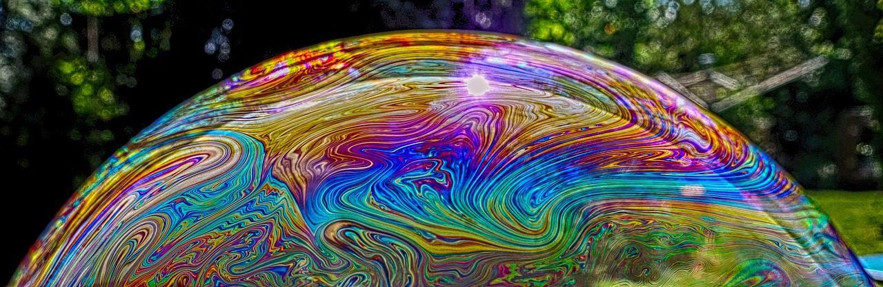 Seifenblase optisch groß in den Vordergrund geholt. Schillert in Regenbogenfarben. Im Hintergrund Rasen und Büsche